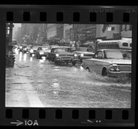 Automobiles driving through flooded streets at Broadway and 7th Street in downtown Los Angeles, Calif., 1965