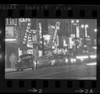 City street scene with neon signs of bars, hotels and theatres along skid row in Los Angeles, Calif., 1965