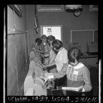 Five women trainees practicing cashiering at Adult Occupational Training Center in Woodland Hills, Calif., 1965
