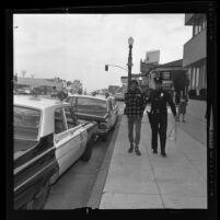 Officer W. B. Duke arresting Stephen LeCover over anti-war sign, Westwood, Calif., 1965