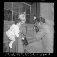 Sammy Davis Jr. taking photo of his wife May Britt and newly adopted son Jeff on steps of Los Angeles County Courthouse, Calif., 1965