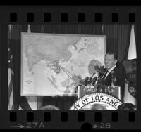 Los Angeles Mayor Samuel W. Yorty pointing at map during press conference about his Southeast Asia trip, 1965