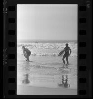Two surfers walking ashore in Santa Monica, Calif., 1965
