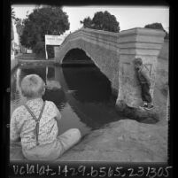 "Two boys playing around bridge over canal in Venice, Calif., sign in background reads ""Venice Canal Improvement Project"", 1965"