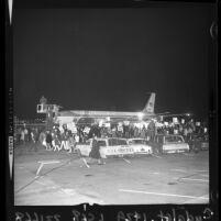 Anti-war demonstrators wave signs at President Lyndon B. Johnson's plane at LAX, 1966