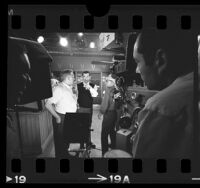 "Actor Jack Webb speaking with cinematographer Walter Strenge on the set of ""Dragnet '66,"" in Calif., 1966"