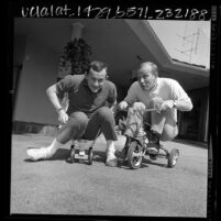 Dick and Tom Smothers playing about on tricycles, Los Angeles, Calif., 1966