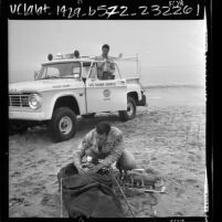 Lifeguards Bob Berson and Jerry Lipman demonstrating resuscitation gear on beach in Los Angeles, Calif., 1966