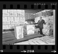 Pasta manufacturer Robert William, standing amid boxes of surplus products, Los Angeles, Calif., 1966