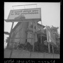 Two billboards in front yard of old house on Wilshire Blvd. in Los Angeles, Calif., 1966