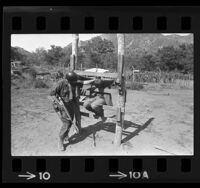 Soldier in wooden stocks at simulated Viet Cong POW camp at Camp Pendleton, Calif., 1966