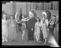 Delaware Indian Betti Haring puts headdress on California Attorney General Robert W. Kenny, 1943