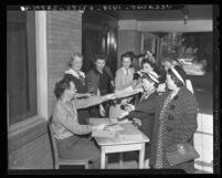 Thomas Heeney hands out applications for enlistment in Women's Army Auxiliary Corps (WAAC) in Los Angeles, Calif., 1942