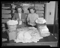 "Two Los Angeles Times employees opening letters from readers who responded to the ""Jap questionnaire,"" 1943"