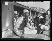 Satchel Paige with bat boys in dugout watching game in Los Angeles, Calif., circa 1943