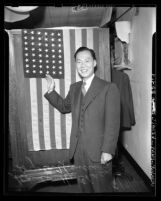 Stanley Chan (Chan Shau Hong) standing before United States flag at his naturalization ceremony in Los Angeles, Calif., 1944