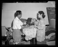 Pacifico Magpione and Mrs. A.B. Cruz sorting clothing for Philippine Relief Society in Los Angeles, Calif., 1945