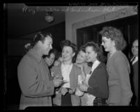 Actor Roy Rogers signing autographs for group of girls at United States Army induction station, 1945
