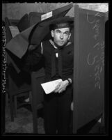 Navy serviceman Robert L. Pierce exiting voting both after casting his absentee ballot, Los Angeles, Calif., 1945