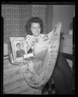 Odena Ervin, widow of Marine Arthur Ervin, displaying Japanese Flag found wrapped around her husband's belongings, 1945