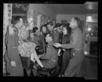 Actresses Betty Hutton and Mona Freeman at piano singing with United States servicemen, 1945