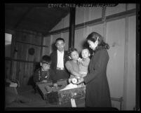 Returning Japanese American internees Masashi Sakatani and his children unpacking in Army barracks in Burbank, Calif., 1945