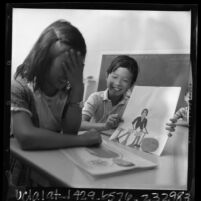 Duane Wong showing Maedon Law a card he made at Elysian Heights School in Los Angeles, Calif., 1966