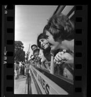 Teenagers, bound for democracy camp, poking their heads out windows of bus in Los Angeles, Calif., 1966