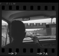 View from inside car and over shoulder of driver of minimum speed limit signs on Harbor Freeway in Los Angeles, Calif., 1966