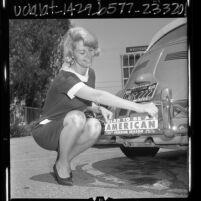 """Lynda Morgan, Miss Freedom Season, placing bumper sticker """"Glad to Be An American"""" on car in Woodland Hills, Calif., 1966"""