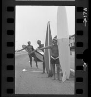 Three male surfers with boards hitch-hiking in Redondo Beach, Calif., 1966