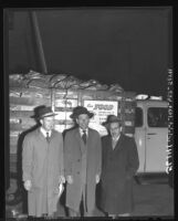 Ben R. Pitcher, James J. Mauget and A. Harry Eisenberg of Los Angeles Jewish Community Council standing beside truck with donated food, 1949