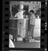 Two boy shoe shiners standing on their boxes to reach a lunch counter in Los Angeles, Calif., 1966