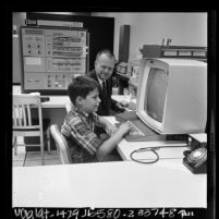 Dr. Robert A. Hayes and his son Robert D. Hayes II at computer terminals, Los Angeles, Calif., 1966