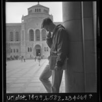 Jeff Smith, a pre-medical student, in reflective pose across from Powell Library on UCLA campus, 1966