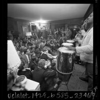 Hugh Masekela performing in Donn Chappellet's living room as crowd watches, Beverly Hills, Calif., 1966