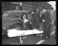 Los Angeles police remove Felipe Rojas from police car to ambulance stretcher after shooting spree in Chinese produce company, 1949