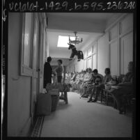 Patients from Mexico waiting in hallway of medical clinic in Calexico, Calif., 1967