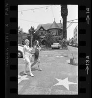 Two women walking past Victorian house of Misses Janes School at 6541 Hollywood Blvd., Hollywood (Los Angeles) 1967