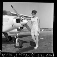 Woman pilot, Mrs. Irwin Title standing in front of single engine plane in Torrance, Calif., 1967