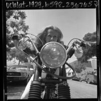 Close-up of Mille Evans riding a motorcycle in Los Angeles, Calif., 1967