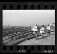 Three striking machinists picketing on hill overlooking freight trains at Taylor Yards in Los Angeles, Calif., 1967