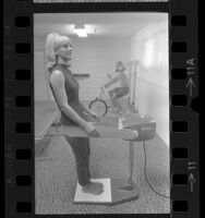 Women using exercise bike and vibrator belt in gym of their Los Angeles apartment complex, 1967