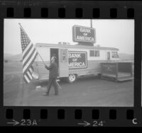 Richard D. Ayers raising flag out front of Bank of America's traveling bank RV in West Covina, Calif., 1967