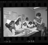 Harriet Goslins conducting a dental assistant training class to seven African American girls in Watts, Calif., 1967