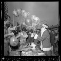 "Man in Santa Claus outfit handing out balloons printed with ""Peace on Earth Stop The War In Vietnam"" in Los Angeles, Calif., 1967"
