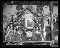 Mexican American women with portrait of Miguel Hidalgo y Costilla on Mexican Independence Day in Los Angeles, 1940