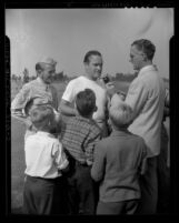 Comedian Bob Hope talking to reporter as children look on at Los Angeles Times War Workers Golf Tournament, 1943