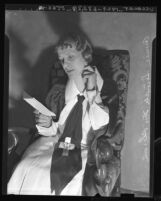 Aimee Semple McPherson seated, reading note demanding $10,000, 1936