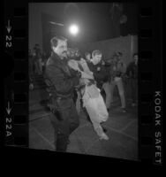 Homeless activist Ted Hayes being removed from Hall of Administration by policemen during Tent City protest in Los Angeles, Calif., 1985